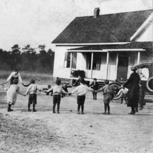 old photograph - children playing outside - schoolhouse