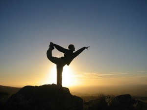 Man doing yoga on a mountain at sunrise