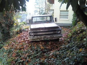 Run-down pickup truck abandoned among the leaves behind a house in the city