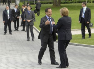 Nicolas Sarkozy and Angela Merkel about to hug each other