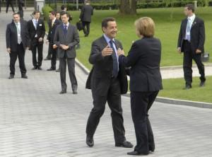 Nicolas Sarkozy and Angela Merkel about to hug each other