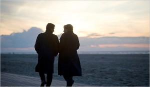 Nicolas Sarkozy and Angela Merkel walking on a beach at sunset