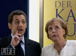 Nicolas Sarkozy and Angela Merkel looking toward the ceiling