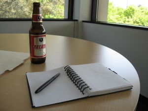 Beer bottle and writing notebook (Flickr by WadeRockett)