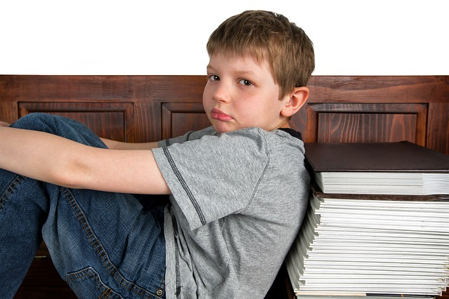 Sad boy leaning against books - a sign of ADHD?
