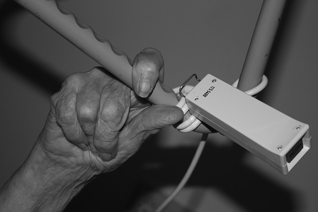 end-of-life care | old woman reaching for emergency button