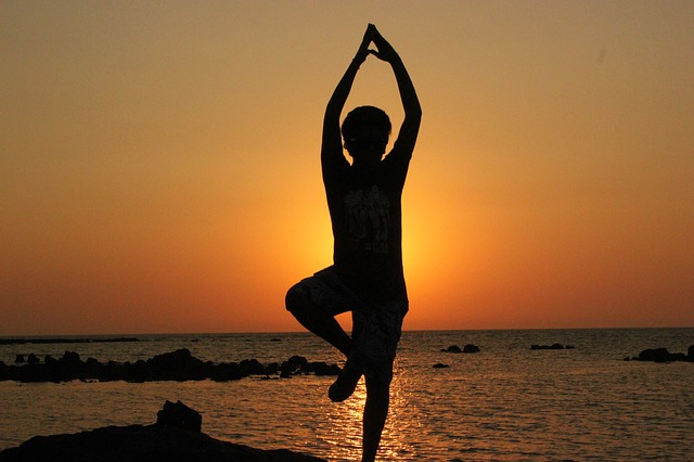 Person doing yoga outdoors at sunset