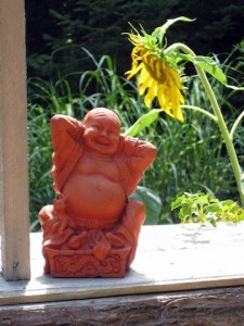 Red Buddha statue and sunflower | Rural Rootz, Ontario (by Shawn Radcliffe)